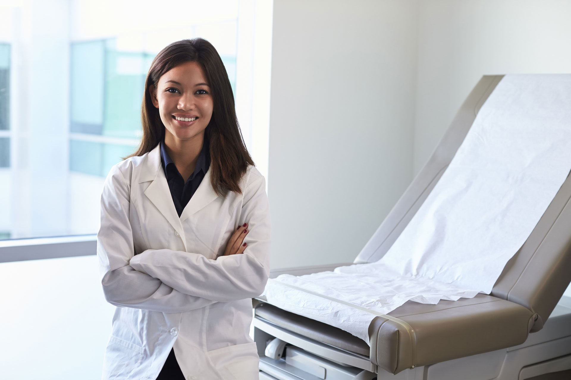 Portrait Of Female Family Nurse Pracitioner Wearing White Coat In Exam Room