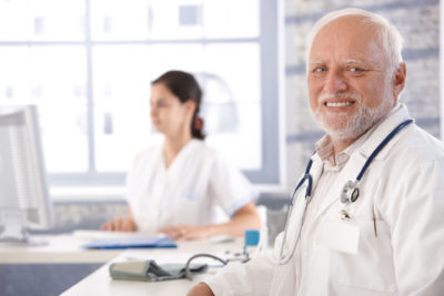 doctor sitting at desk smiling physician shortages