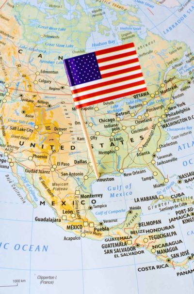 United States of America paper flag pin on a map showing countries and borders