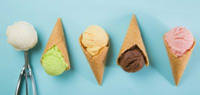 Selection of colorful ice cream scoops on blue background.